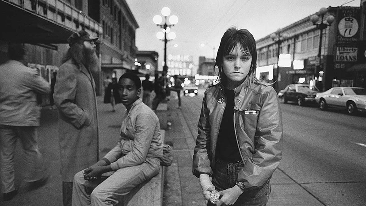 """In a scene from """"Streetwise,"""" a girl looks at the camera"""