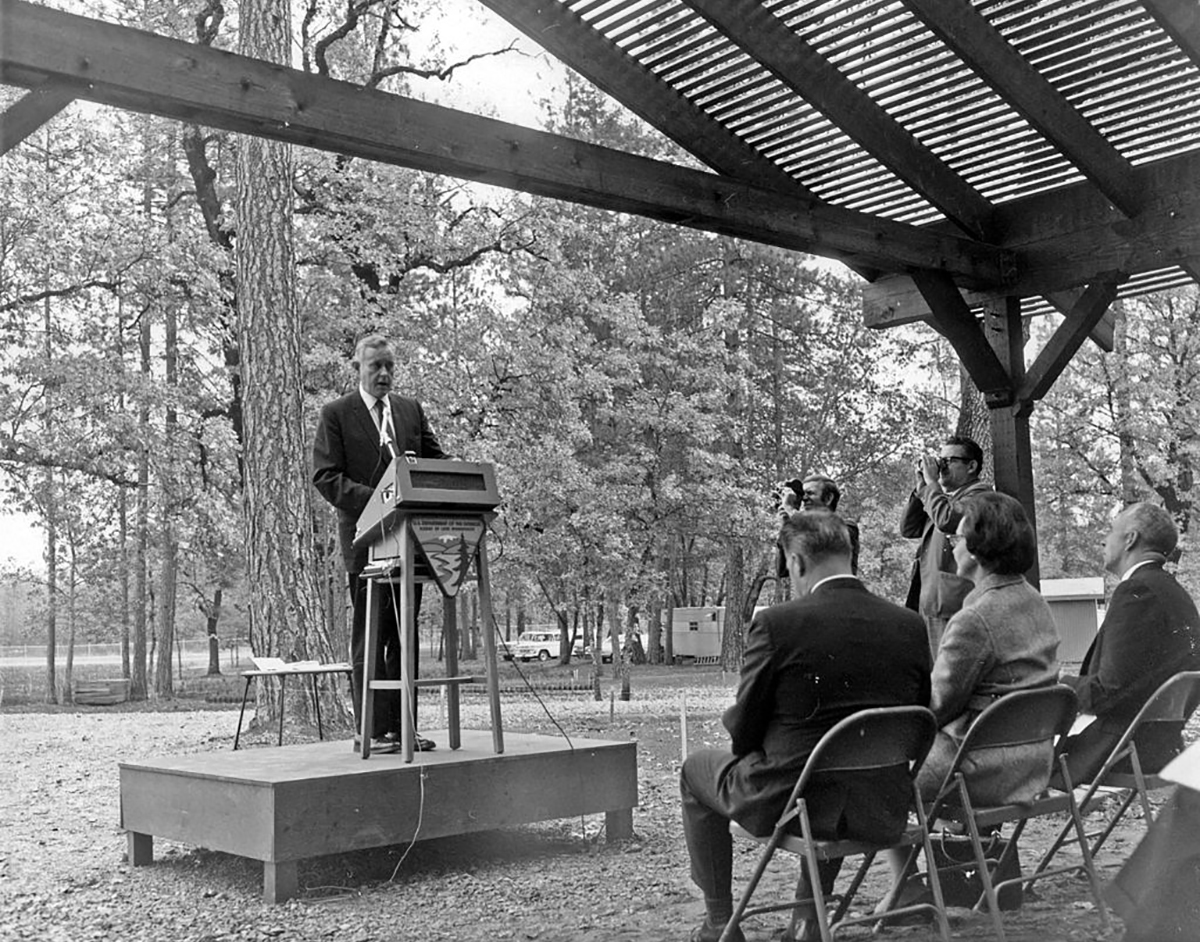 Black and white photo of Tom McCall at a podium outdoors