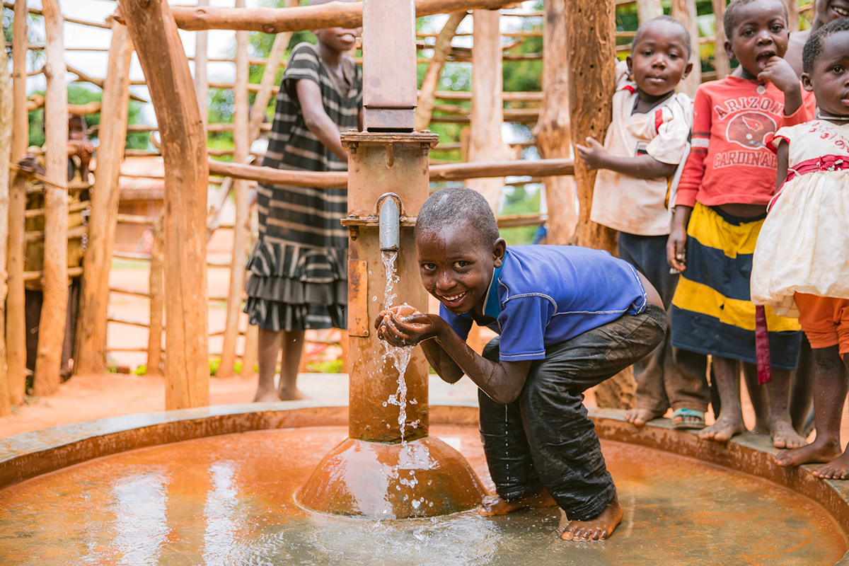 A young boy gets water from a well