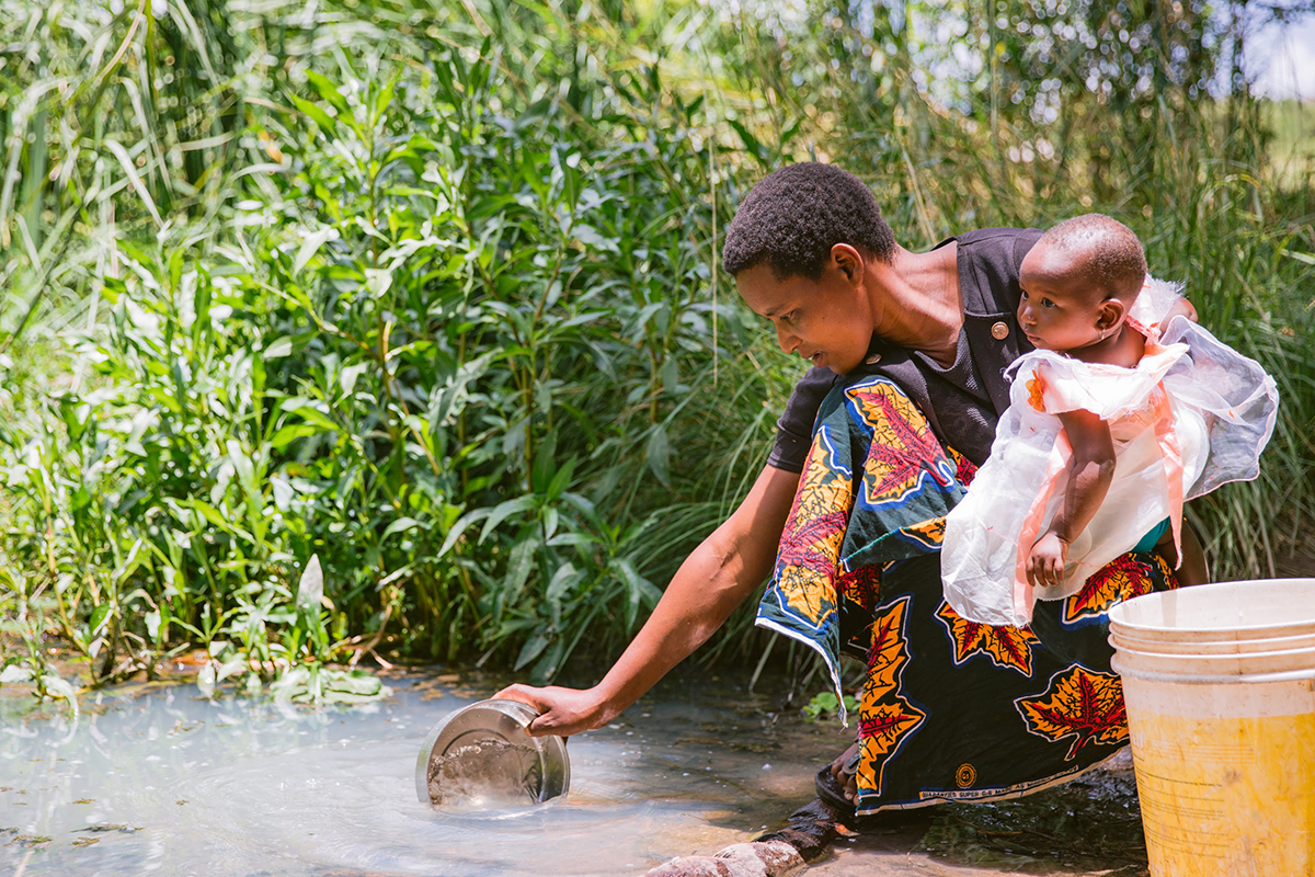 A woman holding an infant scoops up water