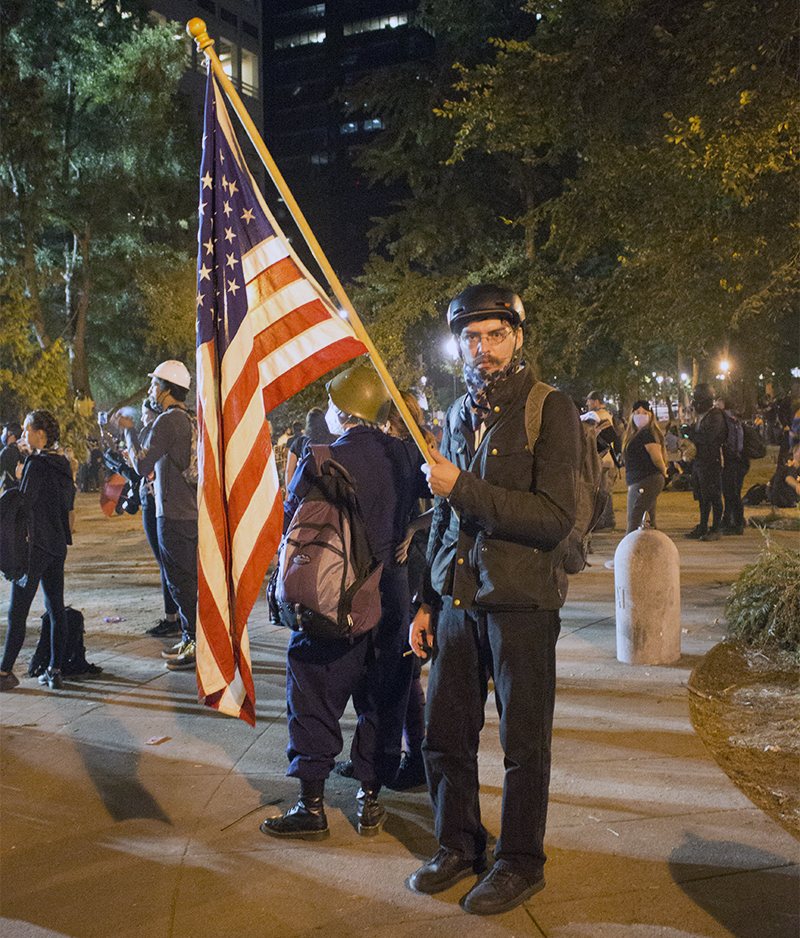 Xander Almeida holds an American flag at a protest