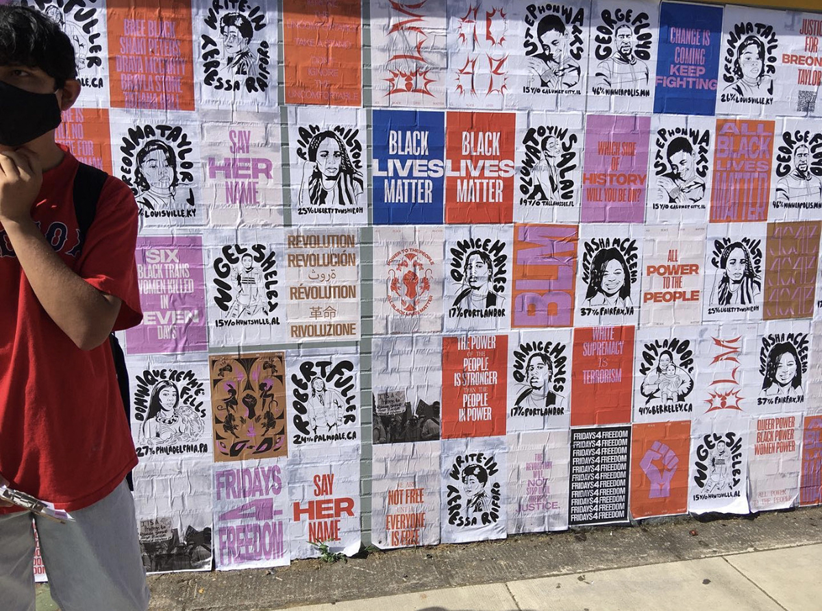 Luis Alonzo Velasco stands next to a wall with social activism posters