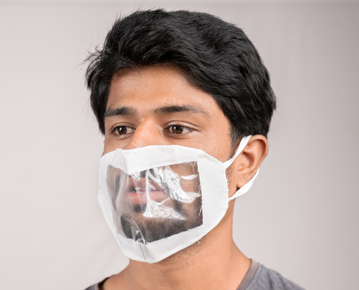Man wears a fabric mask with a transparent plastic panel in front of his mouth.