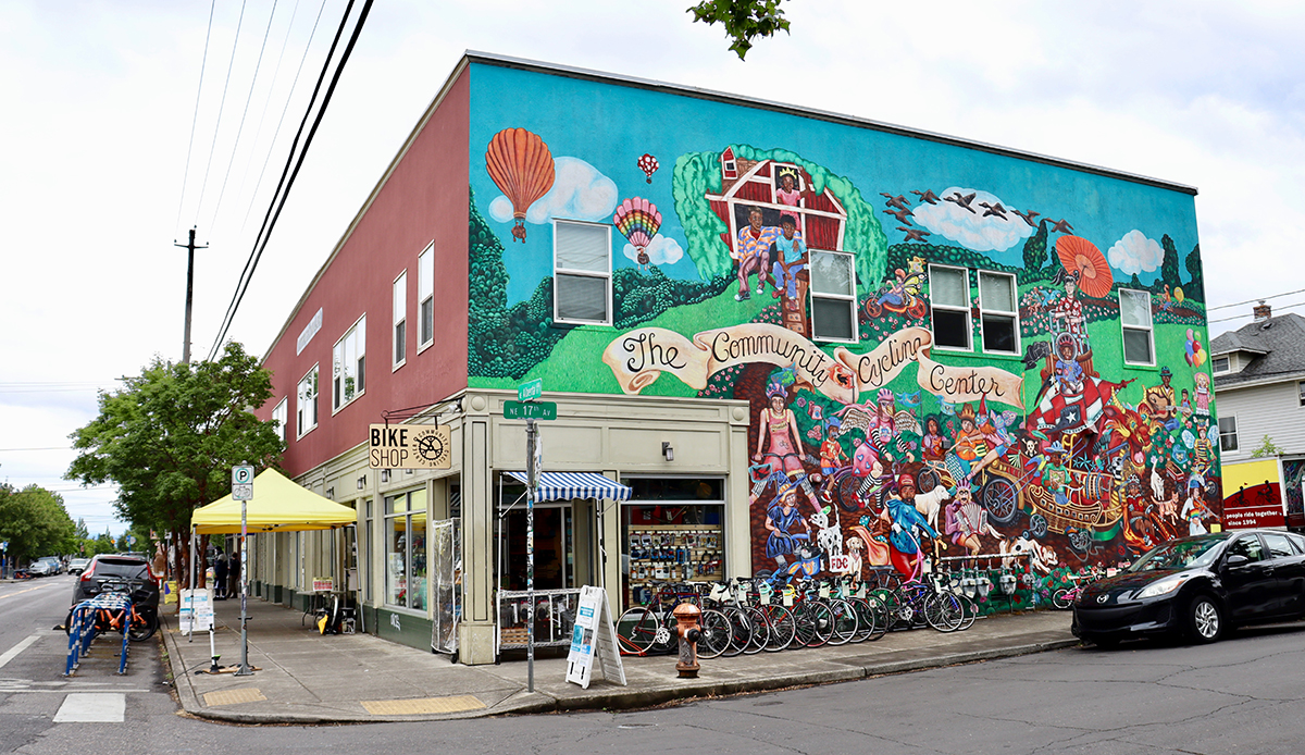 Community Cycling Center exterior, with a mural on the wall and Biketown bikes parked outside