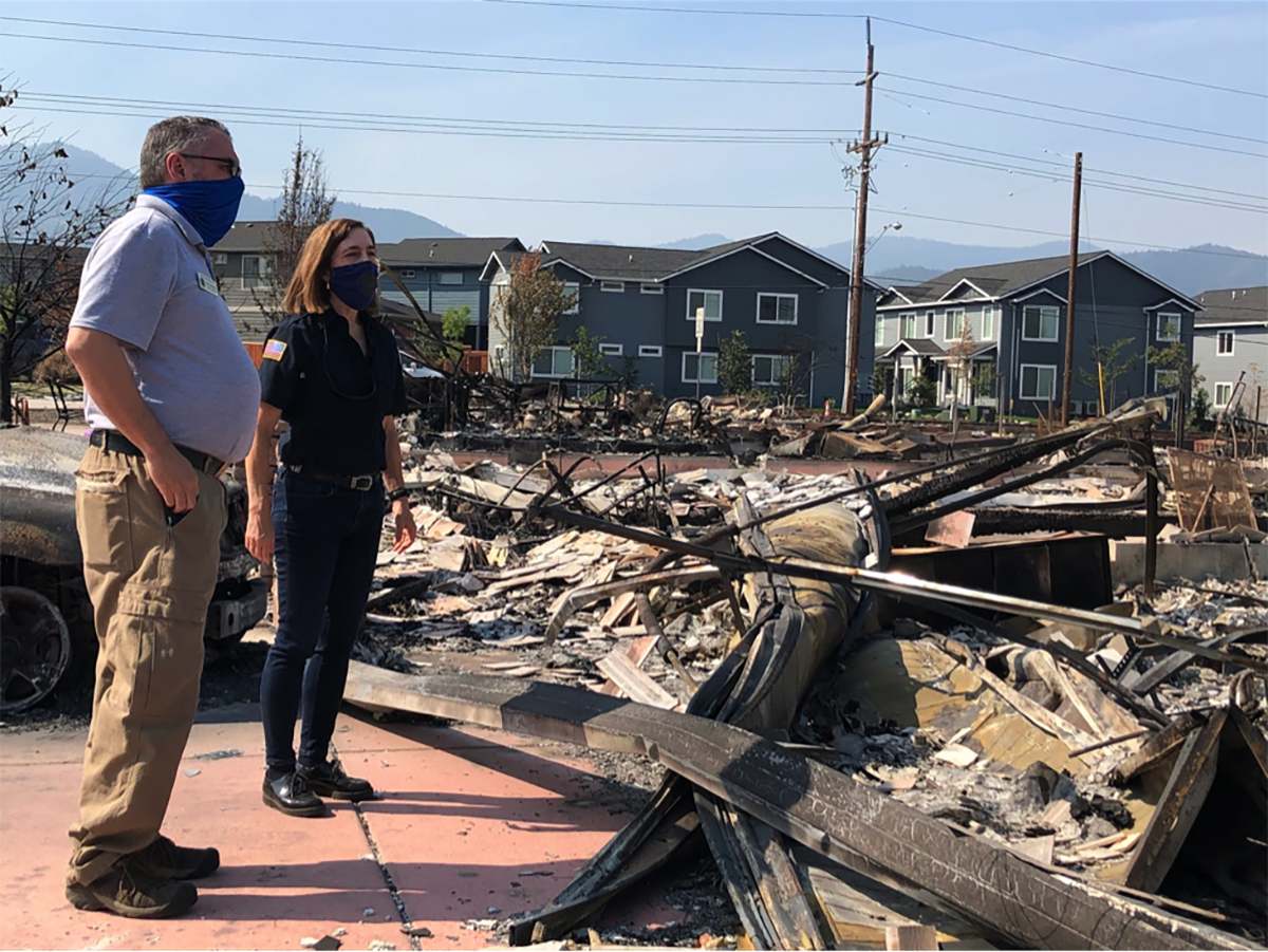 Kate Brown amid rubble from the wildfire