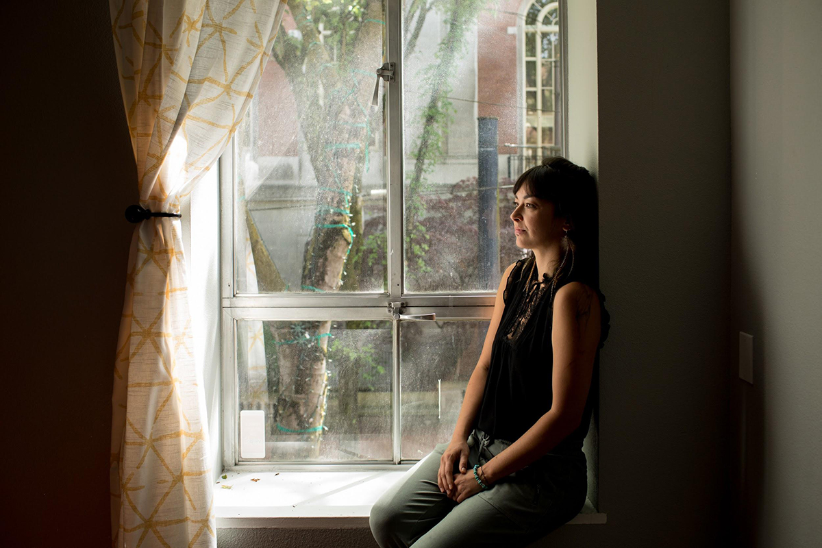 Kristi Carlough sits in front of a window
