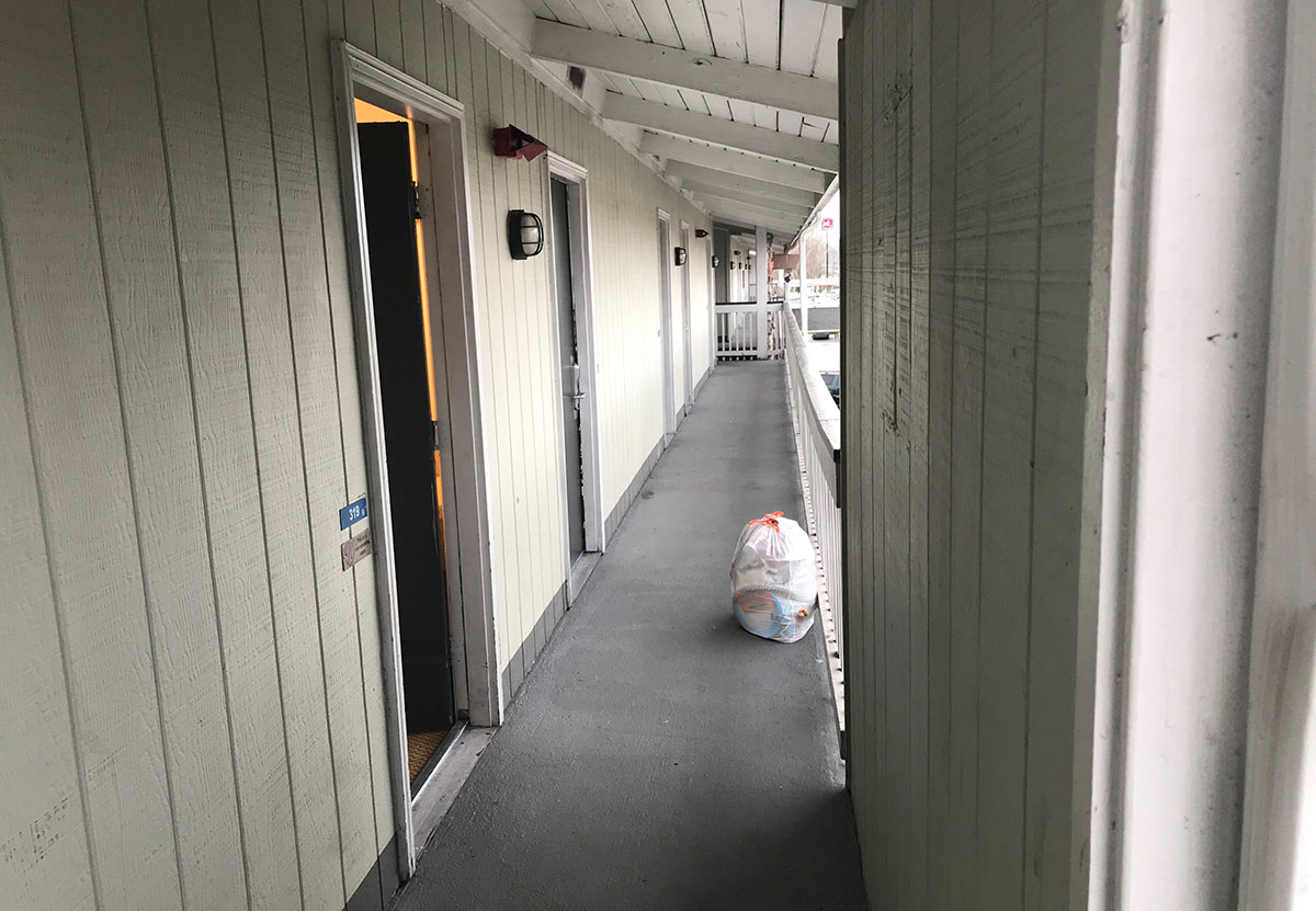 A garbage bag sits on the ground outside a motel room door in the hallway.