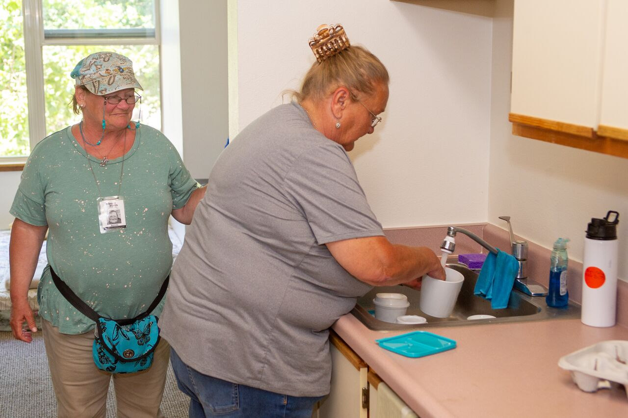 Belinda Estermyer Beason and Karen Flemming tend to dishes.