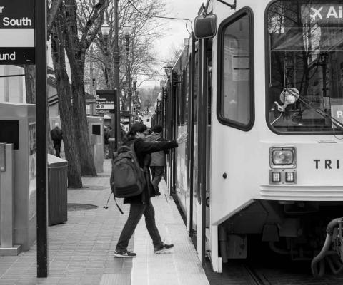 Street Roots photo: A rider boards TriMet's Red Line MAX train in Portland, Oregon