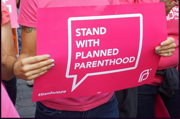 "A woman holds a ""Stand with Planned Parenthood"" sign"