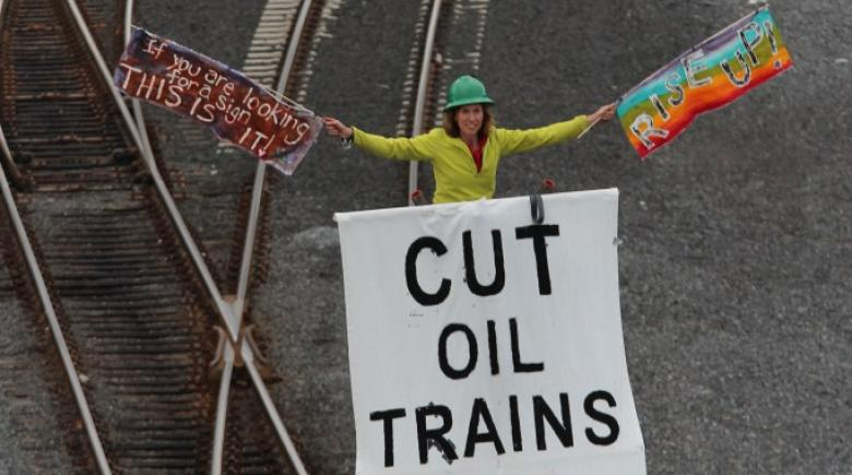 Abby Brockway of Seattle stands on top of an 18-foot tripod to protest poor train safety.