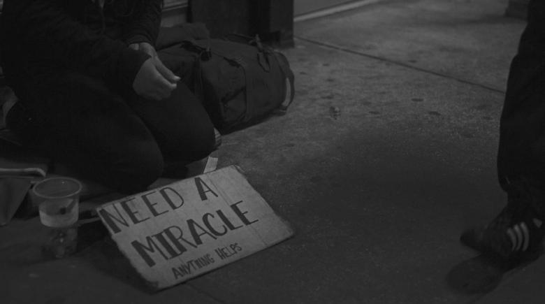 "Sign reads: ""Need a miracle. Anything helps."""