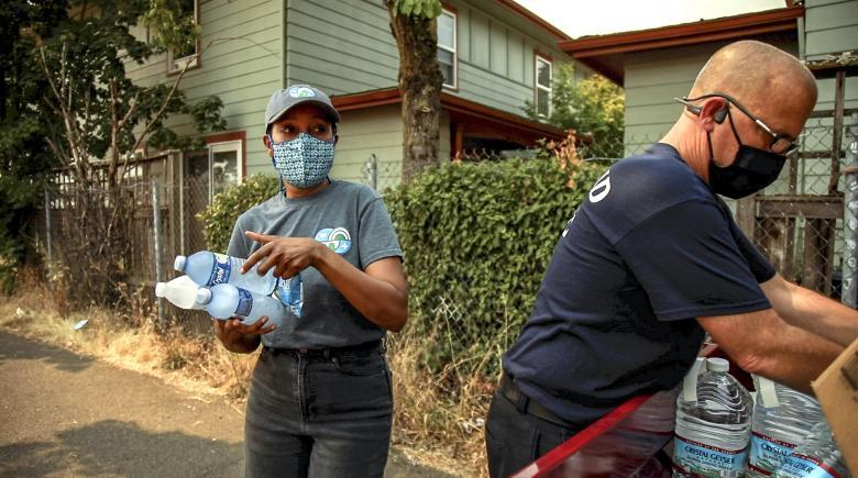 Community health worker Haika Mushi distributes bottled water.