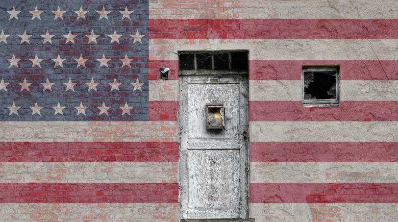 Photo showing exterior wall of building with American flag painted on it and white door in middle