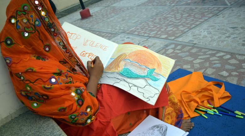 """Girl draws picture with the words """"Stop Violence Against Girls"""""""