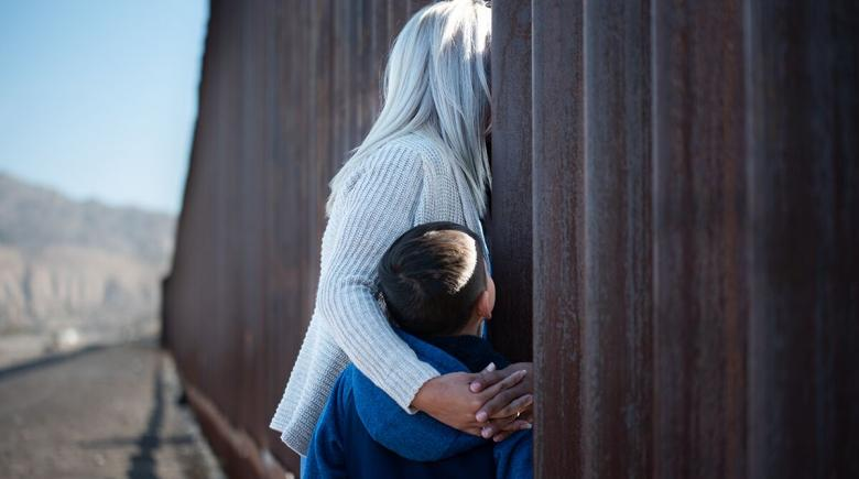 The El Paso Chronicles: A woman with her child meets her spouse on the opposite side of the border wall.
