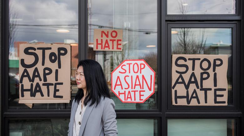 Wanna Lei stands in front of signs posted to a window that read: Stop AAPI hate. No hate. Stop Asian Hate.