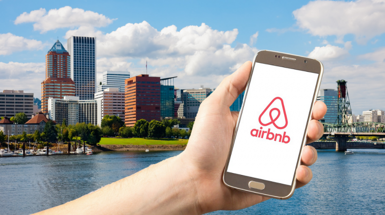 Illustration of phone screen with Airbnb logo, overlooking the Portland skyline