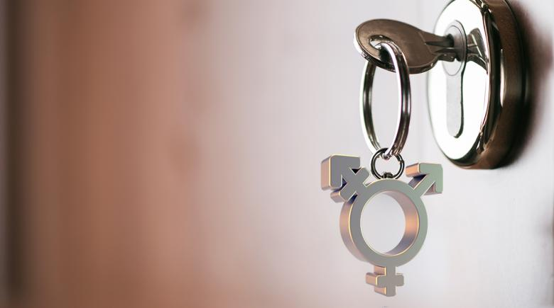 House key with a charm depicting a transgender symbol