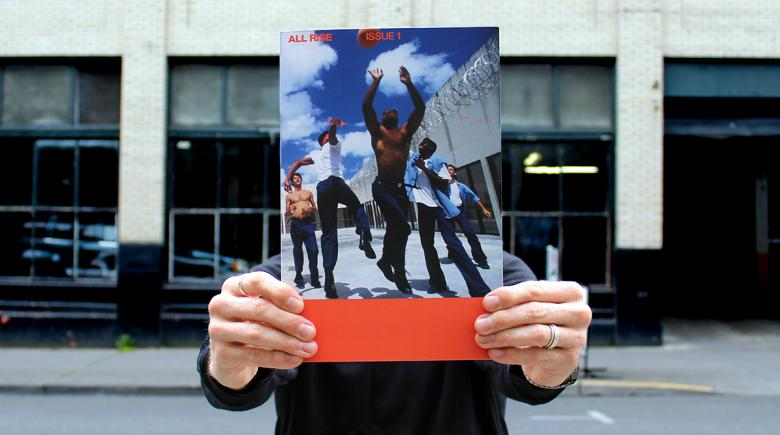 Person holds up the cover of All Rise magazine