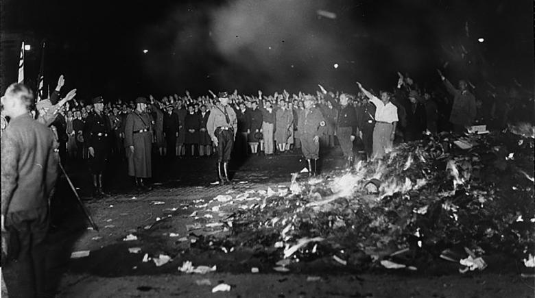 Many people gathered around a pile of burning literature do a Nazi salute