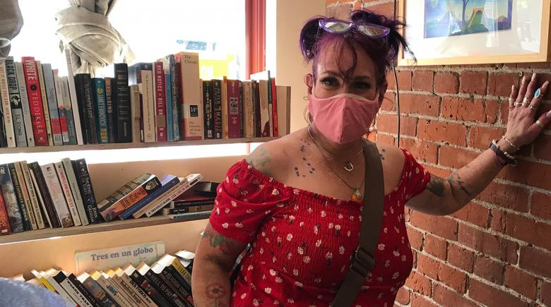 Bronwyn Carver stands beside a bookcase full of books