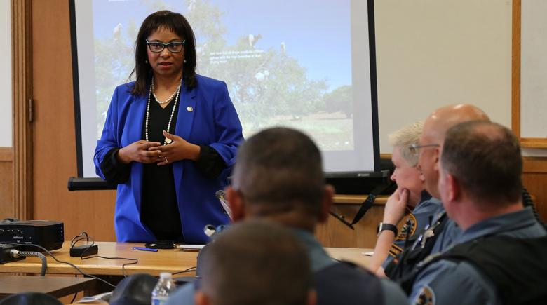 Rep. Janelle Bynum stands in front of a projector, with police officers in the audience