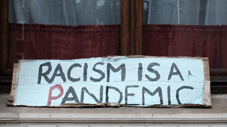 A sign reads: Racism is a pandemic