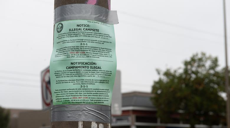 """Photo of a green notice announcing an """"illegal campsite"""" taped to a pole."""