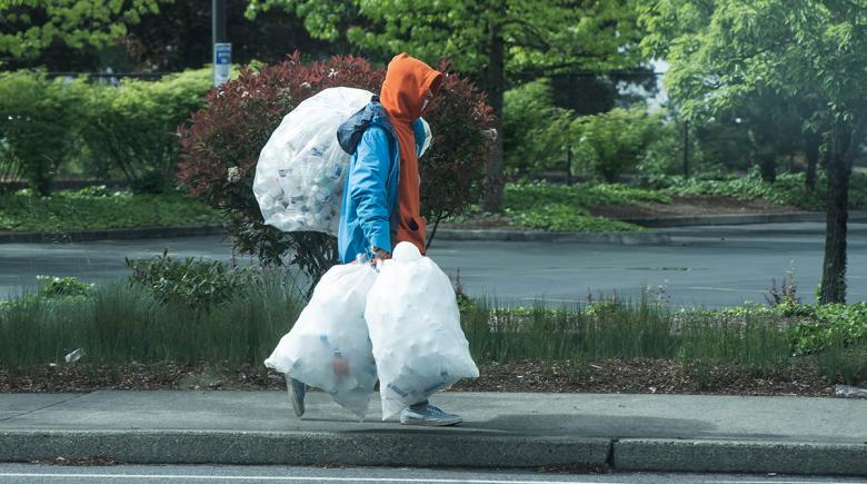A person wearing a hoodie walks on the sidewalk, carrying three garbage bags full of cans and bottles