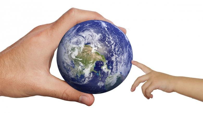 Photo illustration of an adult handing the Earth to a child