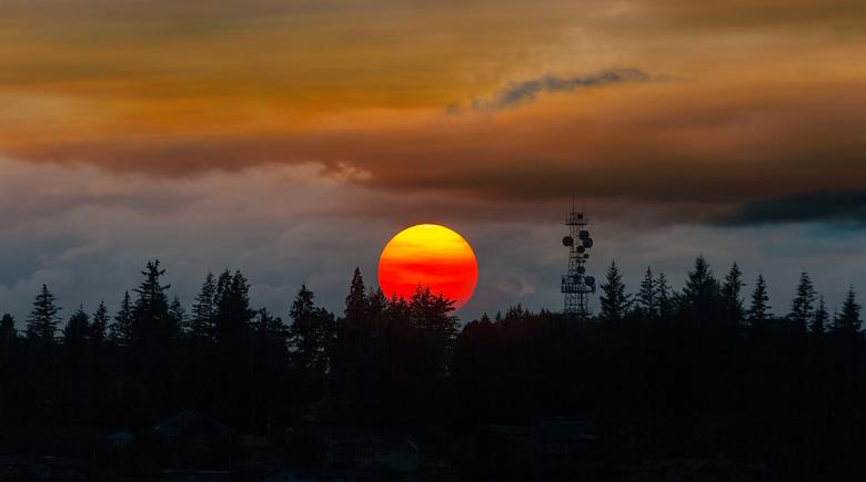The sun sets in a smokey sky