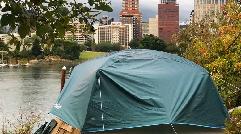 A photo of a tent with the on the eastside esplanade of Portland's waterfront with tall city buildings in the background
