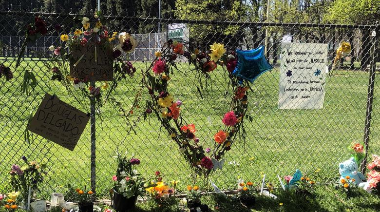 Flowers, signs, candles and other items adorn the site of Robert Delgado's memorial