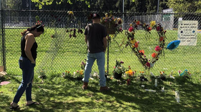Paulette Martin walks past a memorial with flowers and candles