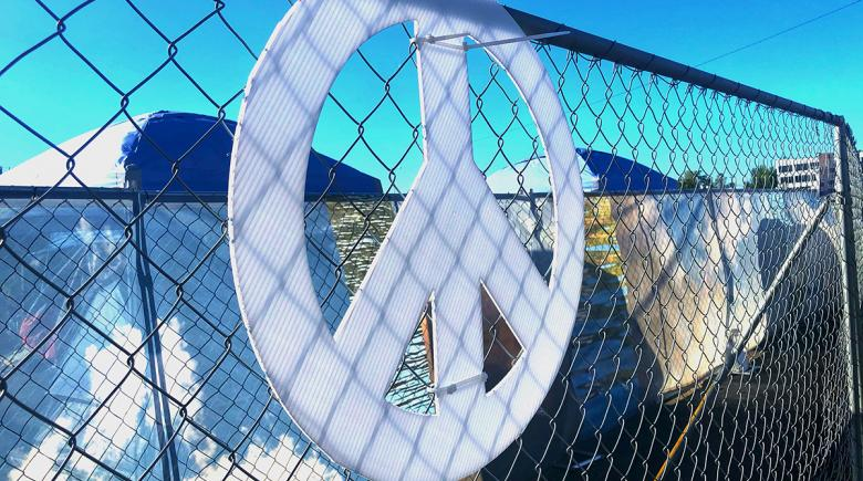 A peace sign hangs on a chain-link fence. Tents are on the other side of the fence.