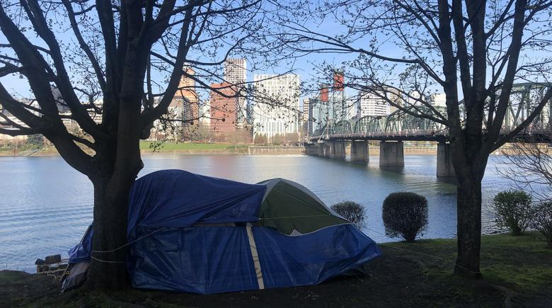 A tent by the river with the Portland skyline as a backdrop