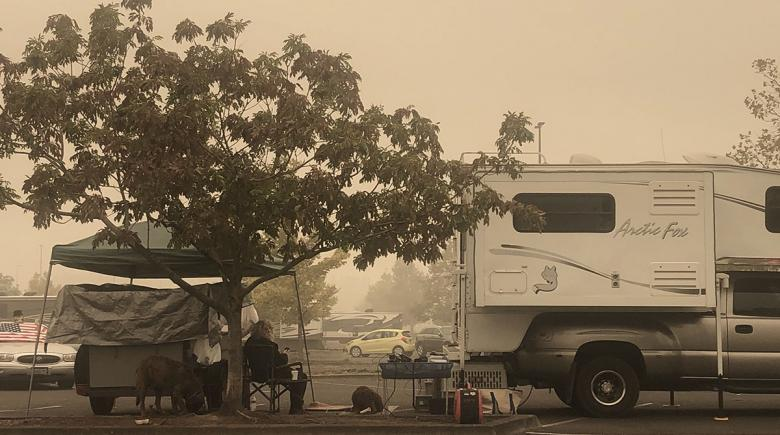 A camper sits beside an RV in a parking lot under an orange hazy sky