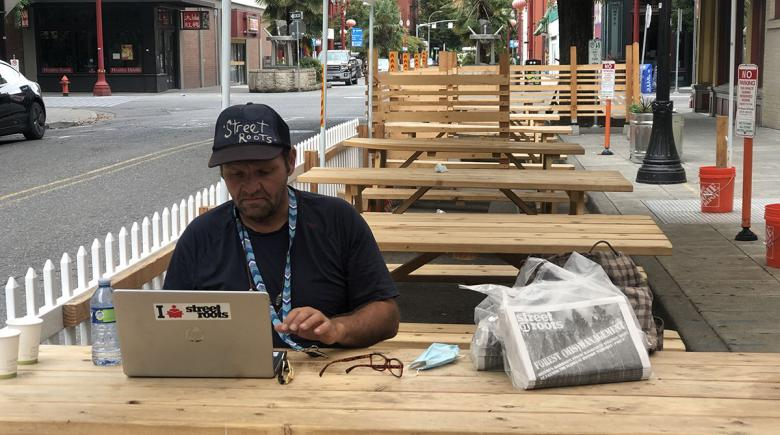 With the keys to his new apartment on a lanyard around his neck, Dan Newth works on his column for Street Roots.