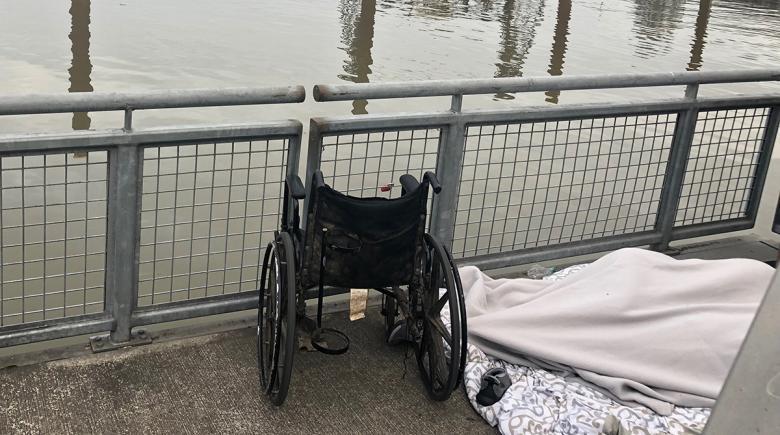 A person sleeps beside a wheelchair