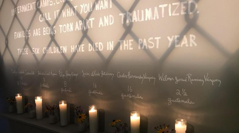 Message on a wall, with candles and flowers memorializing six children who have died