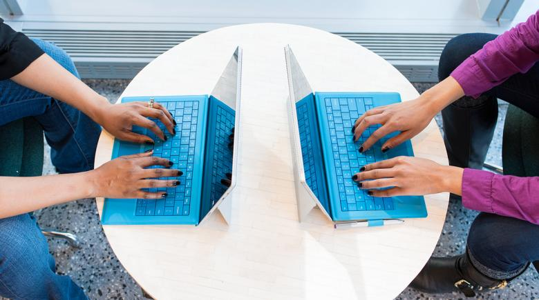 Two people using computers