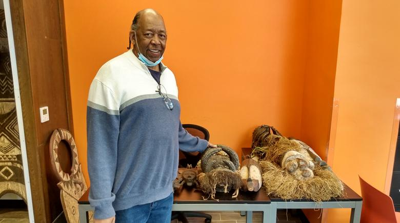 Willie Fiers stands next to a table with African masks at Flip the Script's new space