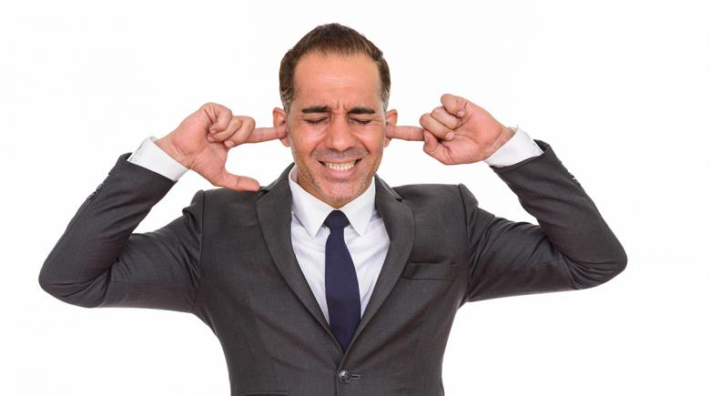 A man in a suit with his fingers in his ears