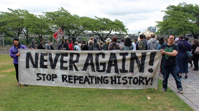 "Sign displays ""Never Again! Stop Repeating History"""