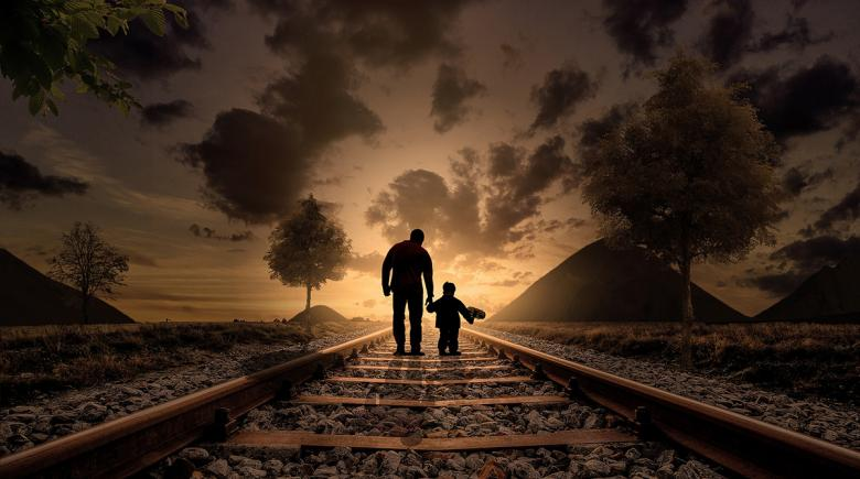 A photo illustration shows the silhouette of adult with a child walking on train tracks