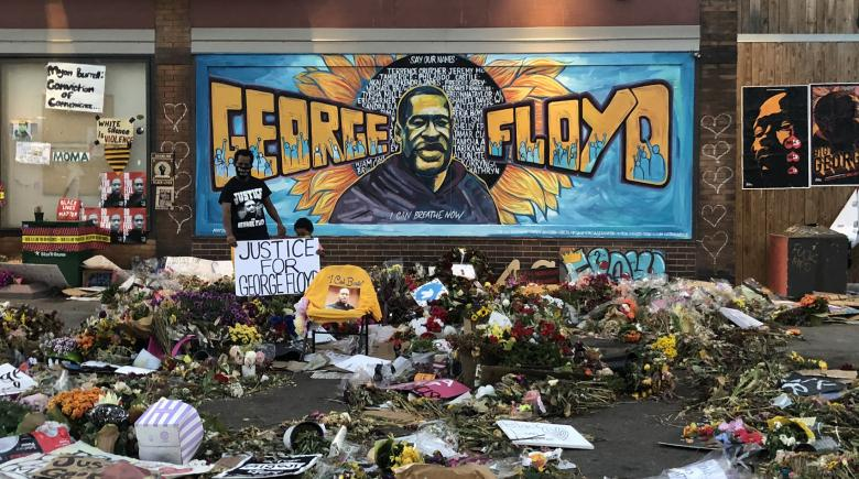 Mural of George Floyd painted on the wall, behind a sea of memorabilia and Black Lives Matter messages