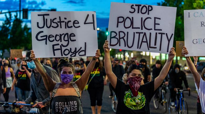 People march, holding signs that read: Justice 4 George Floyd. Stop police brutality.
