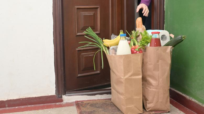 Groceries are delivered in front of someone's apartment door