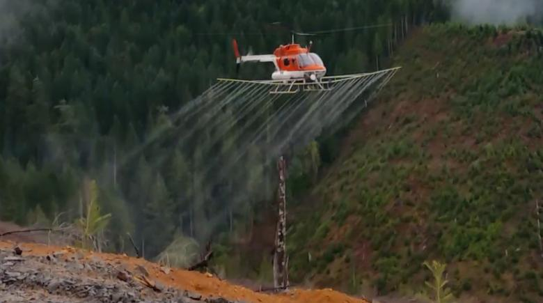 A helicopter sprays herbicide